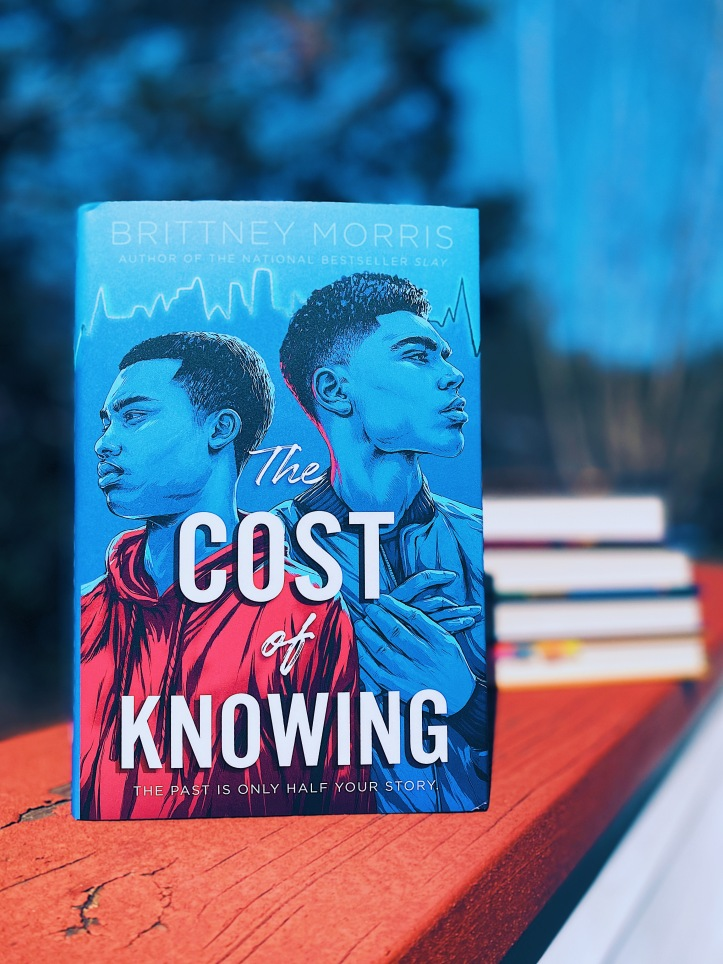 Picture of front-facing THE COST OF KNOWING by Brittney Morris with blurred background and books in background.